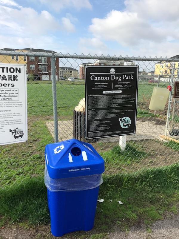 Blue recycling bin in-front of a fenced in park area