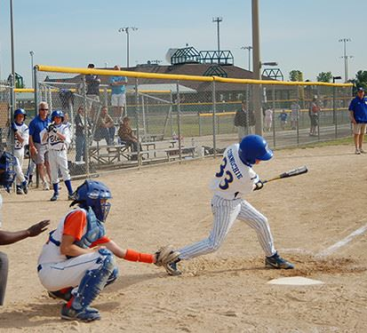 Young Person Swinging Bat During Baseball Game